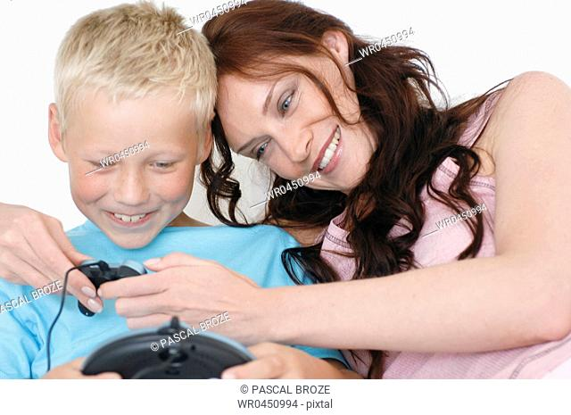 Close-up of a mid adult woman and her son playing a video game and smiling