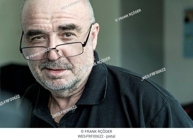 Portrait of senior man with stubble wearing glasses
