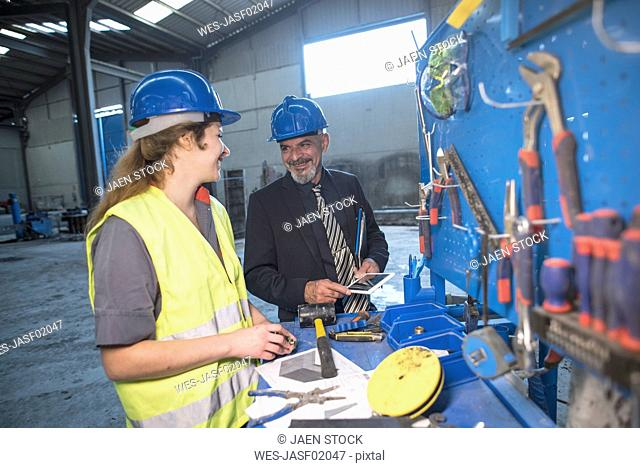 Smiling businessman talking with female worker in factory