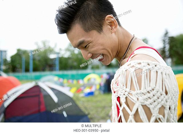 Laughing young man looking down at summer music festival campsite