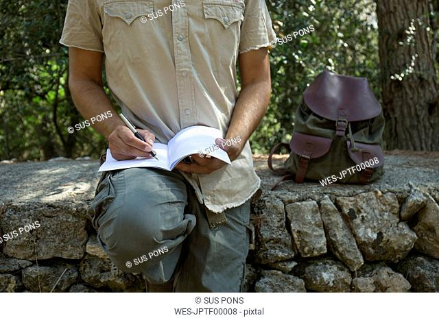 Man with backpack sitting on a wall in nature writing in notebook, partial view