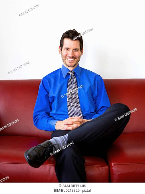 Mixed race businessman smiling on sofa