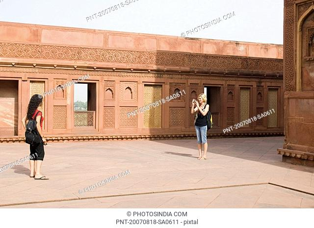 Young woman taking a picture of her friend, Taj Mahal, Agra, Uttar Pradesh, India
