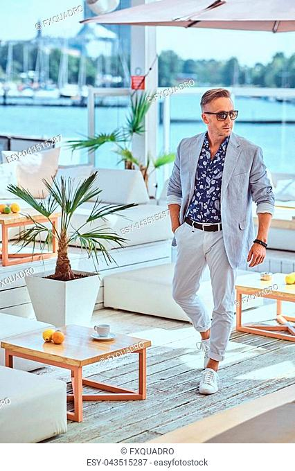 Fashionable rich man with stylish hair dressed in modern elegant clothes at outdoor restaurant against the background of the city wharf
