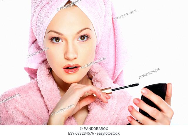 Beautiful redheaded girl in pink clothes isolated on a white background, cosmeticology, SPA