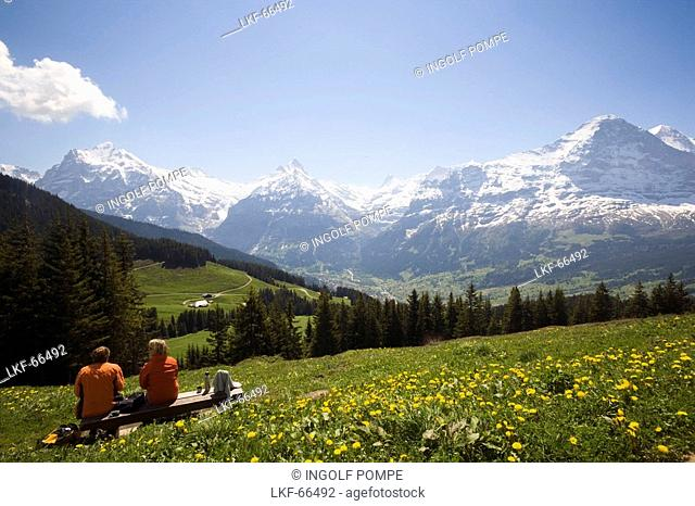 Hikers resting at Bussalp 1800 m, view to Eiger North Face 3970 m, Grindelwald, Bernese Oberland highlands, Canton of Bern, Switzerland