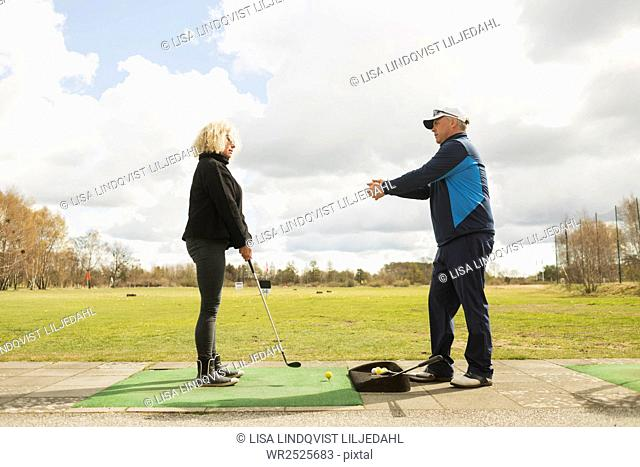 Man assisting woman in playing golf at driving range