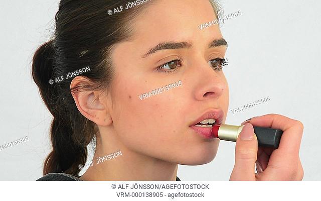 Young woman, 25 years, applying lipstick