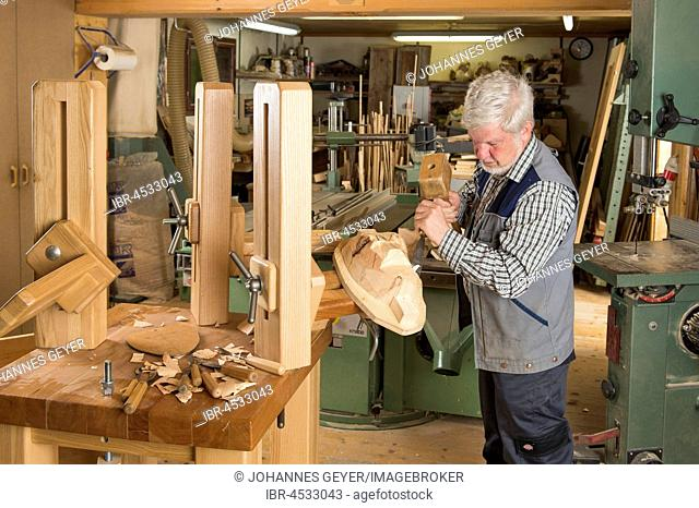 Wooden mask carver using wood carving tools on a wooden block, wooden mask carver, workbench, Bad Aussee, Styria, Austria