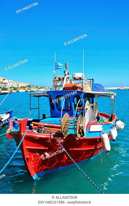 Greek fishing boat in Sitia. Traditional Greek boat in red and blue colors bobs on the waves on a clear sunny day. Port of Sitia, Crete