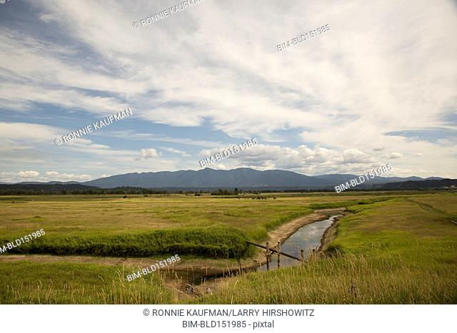 Clouds over river and fields in rural landscape