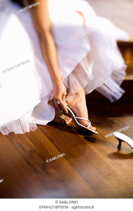 Bride reaching down to take off shoes, selective focus