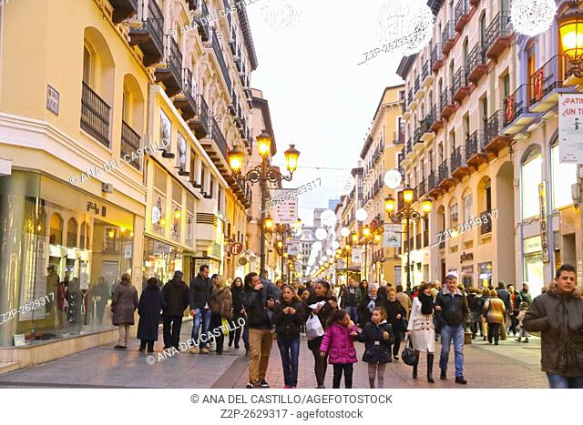 ZARAGOZA, SPAIN- JANUARY 1, 2016: People walking down the boulevard Alfonso I to plaza del Pilar. Christmas decoration at dusk