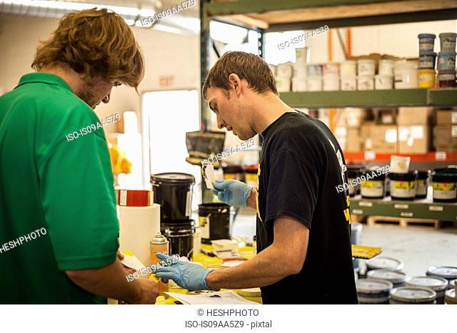 Workers checking inks in screen printing workshop