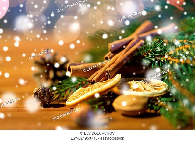 decoration, winter, holidays and new year concept - close up of christmas fir branch with cinnamon and dried orange on wooden table