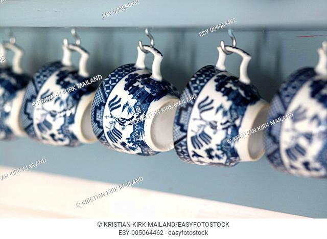 Old fashioned coffee cups hanging from lihgt blue shelf
