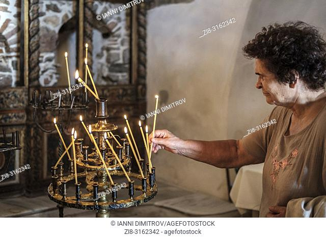 Bulgaria,Senior woman lighting a candle in orthodox church