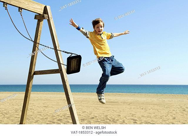 Boy jumping off swing at beach