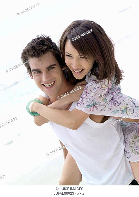 Man giving woman piggyback ride at beach