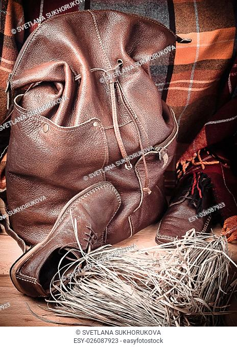 Leather backpack and shoes on the background of wool tartan on the wooden floor
