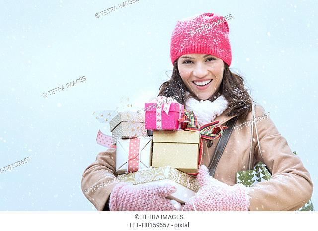 Portrait of woman in winter clothes carrying presents