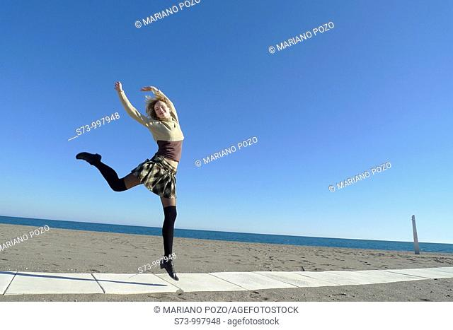 Woman jumping in Torremolinos beach, Malaga province, Andalusia, Spain
