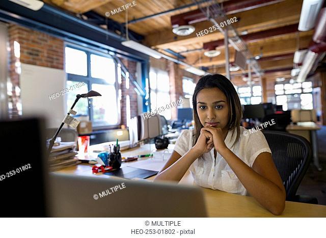 Focused businesswoman using laptop in office