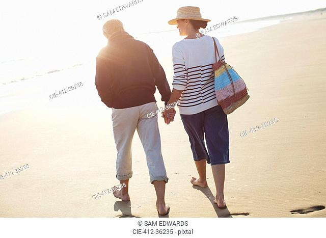 Barefoot mature couple holding hands and walking on sunny beach