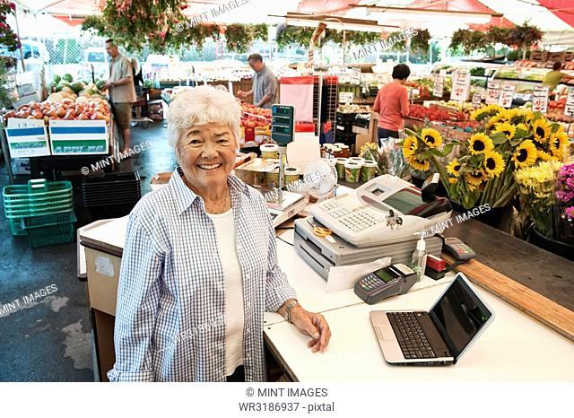 Senior woman standing at the checkout of a food and vegetable market, smiling at camera