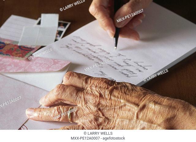 senior hands writing a letter
