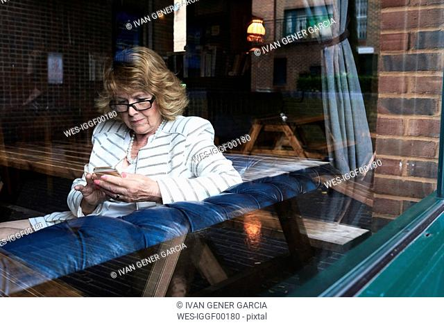 Senior businesswoman checking cell phone in a coffee shop