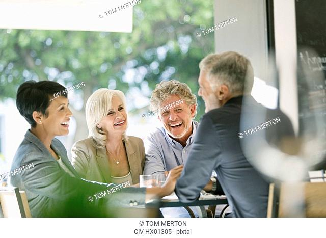 Smiling couples talking and dining at restaurant table