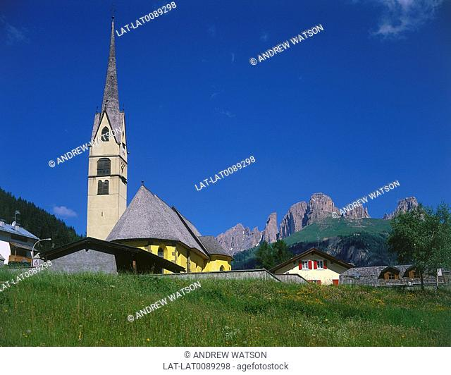 Trentino. Alba village church spire. View to Sassolungo rock formations,pillars