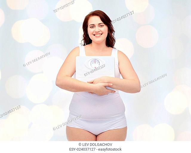 weight loss, diet, slimming, plus size and people concept - happy young plus size woman in underwear holding scales over holidays lights background