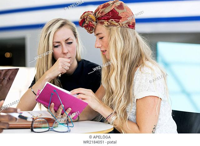 Female friends reading notes together in college cafe