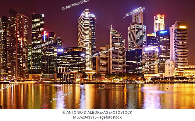 aerial view of the Central Business District by night. In the foreground the water of Marina bay. Singapore