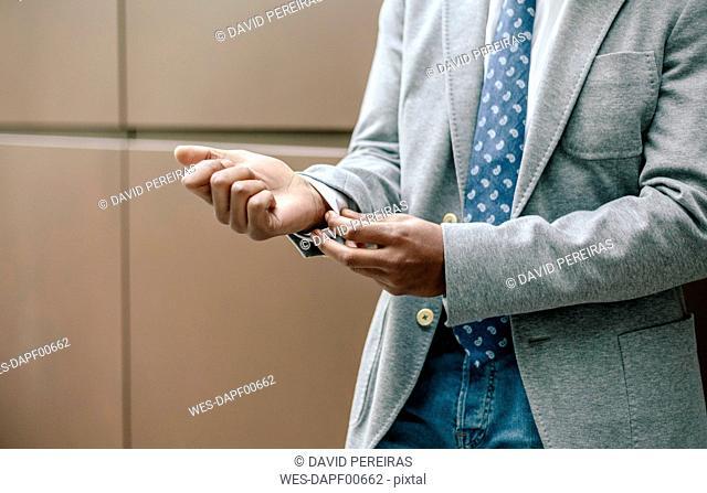 Businessman adjusting cuffs, close up