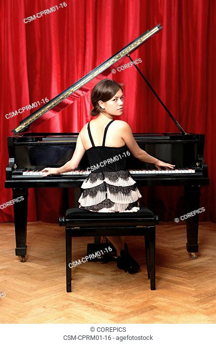 Beautiful pianist looking over her shoulder whilst playing on a grand piano