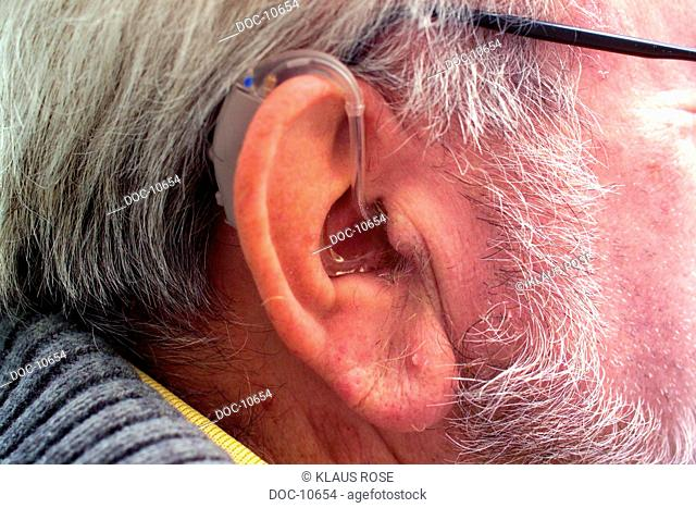 Ear of older man with deaf-aid