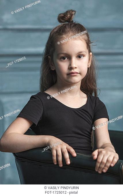 Portrait of cute girl sitting on armchair at home