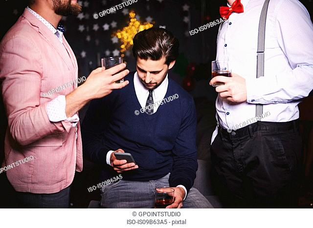 Three men at party, man in middle using smartphone
