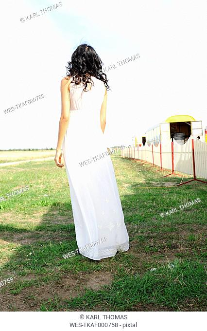Dark-haired young woman wearing white dress standing on a meadow