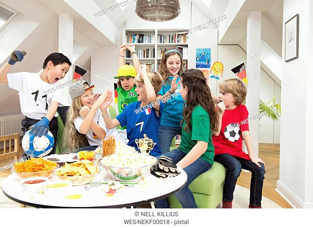 Group of kids watching soccer world championship with table full of sweets and snacks