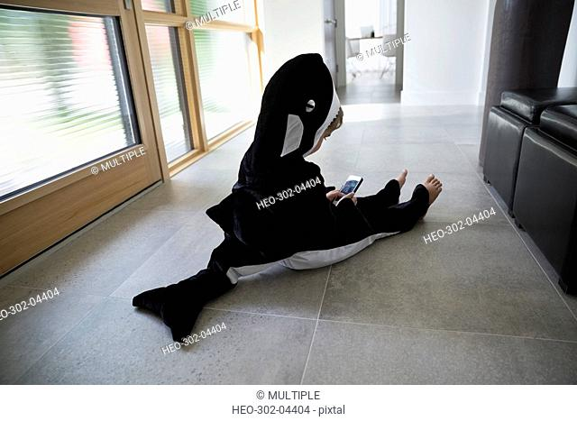 Boy in killer whale costume sitting on floor with cell phone in foyer