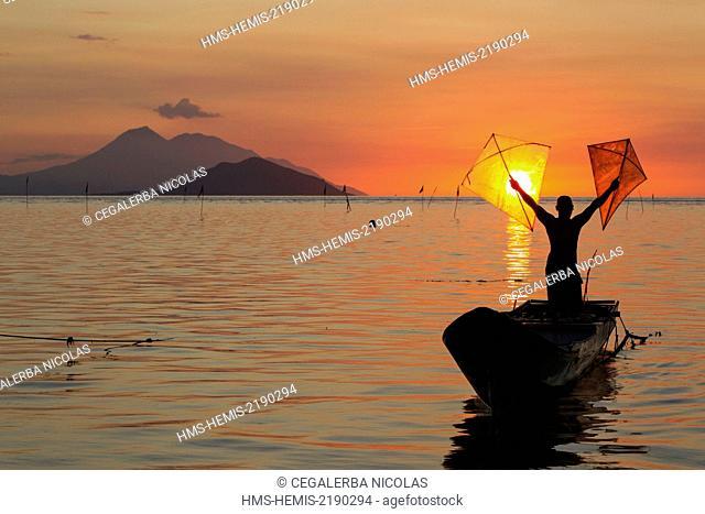 Indonesia, Lesser Sunda Islands, Alor archipelago, Pantar Island, Kabir, fisherman holding proudly his fishing kites at sunset with Batang Island and Lambata...