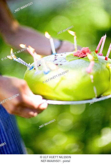 Woman holding birthday cake with lit candles, close-up