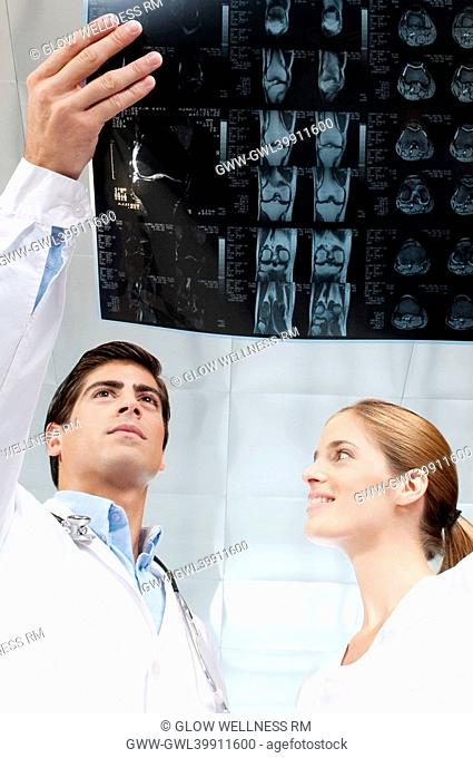 Doctor and a female nurse examining an x-ray report