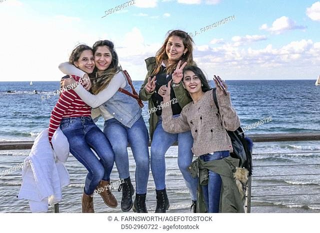 TEL AVIV ISRAEL Young Arab girls hamming it up for the photographer on the beach