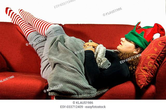 Beautiful girl is sleeping with green and red elf hat and stripes sock in a red sofà