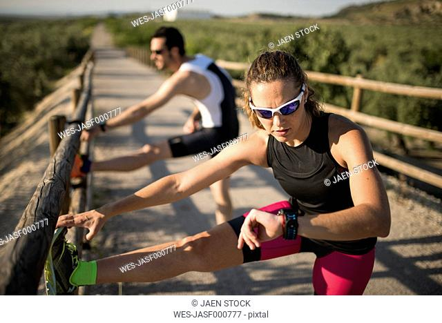 Sportive woman with smartwatch and man stretching on a bridge